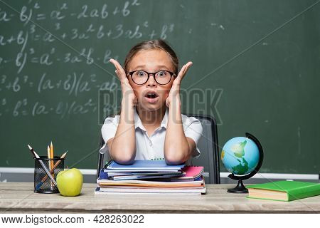 Shocked Schoolkid With Open Mouth Looking At Camera Near Notebooks And Blurred Chalkboard