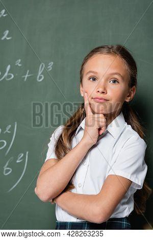 Thoughtful Schoolkid Looking At Camera Near Chalkboard In School