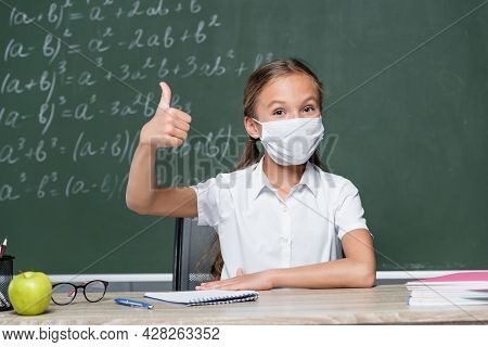 Schoolkid In Medical Mask Showing Thumb Up Near Apple, Notebook And Chalkboard On Blurred Background