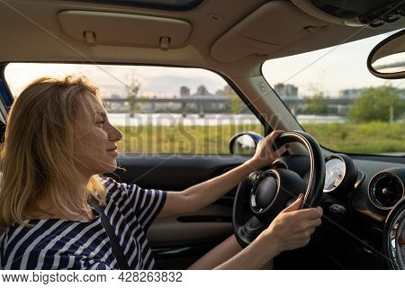 Portrait Of Carefree European Middle Woman Driving Car, Smiling, Happy During The Drive At Sunset. S