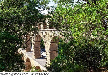 The Pont du Gard is the tallest Roman aqueduct. The aqueduct Pont du Gard connects hills covered with dense deciduous forest. The bright sunny day. Interesting trip to France.