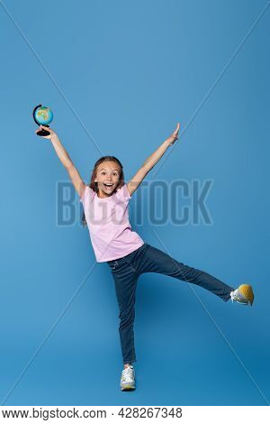 Positive Schoolkid In T-shirt Holding Globe On Blue Background