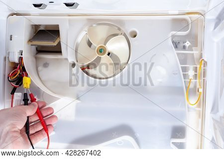 A Technician Checks An Electrician With A Digital Multimeter In Refrigerator Fridge. Inside Refriger