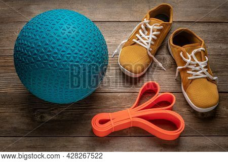 heavy rubber slam ball filled with sand, resistance band and minimalist barefoot sneakers on a rustic wooden deck, exercise and fitness concept
