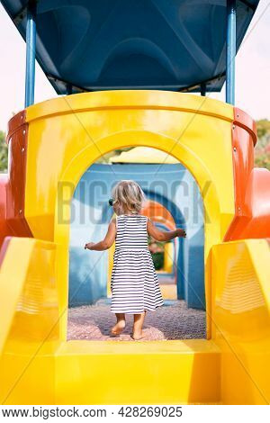 Little Girl Entered The Toy House On The Playground. Back View