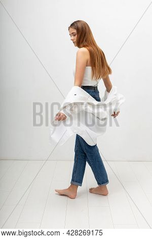 Young Attractive Caucasian Woman With Long Brown Hair In Corset, Shirt, Blue Jeans On White Studio B