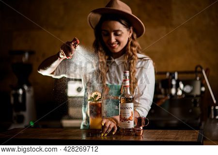 Ukraine, Kyiv - May 19, 2021: Bottle Of Syrup, Cups And Glass Of Drink On Table And Handsome Woman S