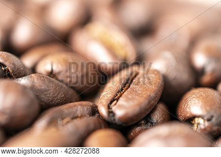 A Macro Photo Of Fried Brown Coffee Beans On The Table. Freshly Roasted Coffee Beans Background
