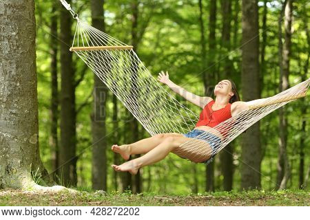 Excited Woman Swinging On Hammock Celebrating Vacation In A Beautiful Green Forest