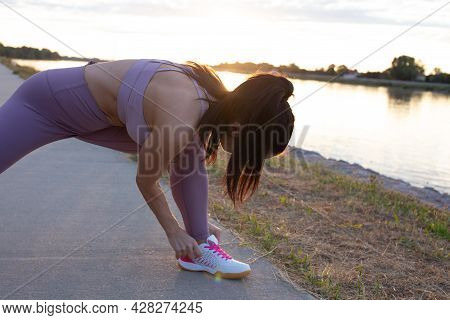 Woman In Sportswear Adjusting Shoes Before Running At Riverside