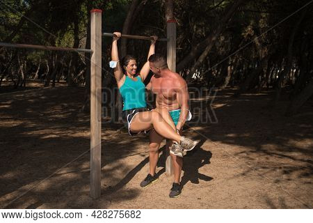 Trainer Helping A Fit Young Woman To Do Pull-up Her Arms On The Park. Sport Actuvity To Stay Healthy