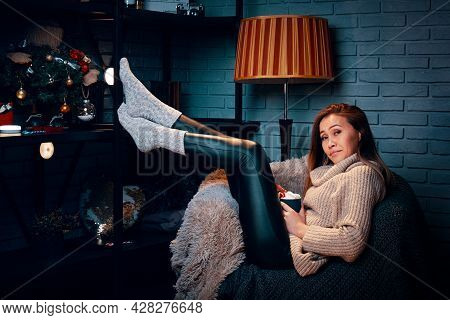 Woman Holding Hot Chocolate With Marshmallows Sitting On Chair. Christmas Tree With Decorations On S