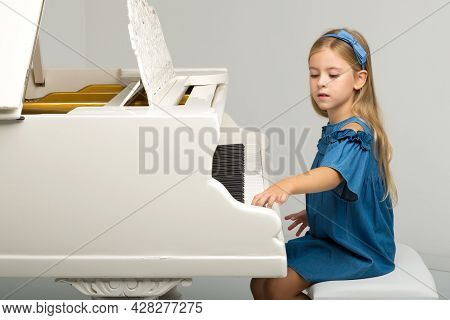 Charming Girl Posing At Grand Piano. Portrait Of Smiling Six Or Seven Years Old Girl Posing At Music