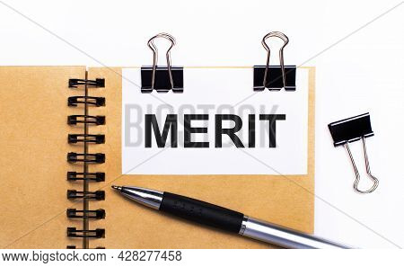 On A Light Background, A Brown Notebook With A Pen, Black Clips And A White Card With The Text Merit