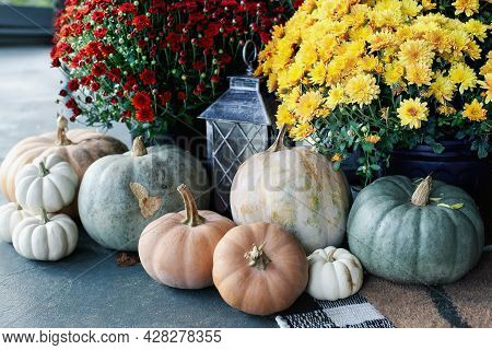 Red And Yellow Orange Mums On A Front Porch That Has Been Decorated For Autumn With Heirloom White,