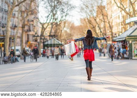 Happy shopping woman walking with bags on Barcelona, La Rambla famous street. Shopper with open arms up in freedom and happiness. From the tourist landmark in Catalonia, Spain.