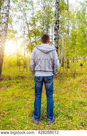 Rear View Of A Young Man In The Forest Alone