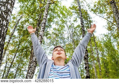 Young Man With Hands Up On The Nature Background