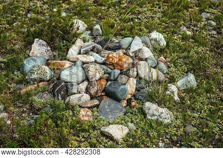 Pile Of Stones With Lichen And Moss On Green Grass. Art Nature Background With Many Stones On Ground