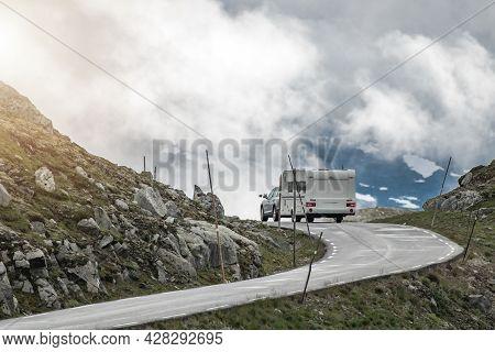 Modern Car Pulling Travel Trailer On The Scenic Alpine Road. Rv Caravaning Theme.