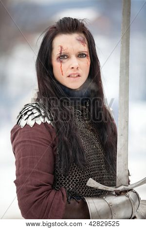 Woman in the medieval costume holding a sword