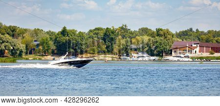 The Motor Boat Moves Quickly Along The Water Surface Of The River. In The Background, The Coastline