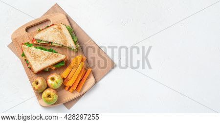 Sandwiches, Apples And Carrots On A Board On A Kraft Bag On A Gray Background. Preparing A School Lu