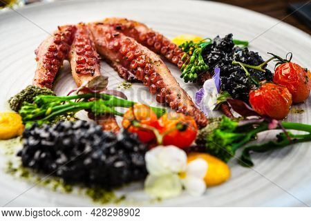 Octopus with black risotto. Carrot cream, mini-broccoli, basil pesto. Delicious healthy traditional food closeup served for lunch in modern gourmet cuisine restaurant.