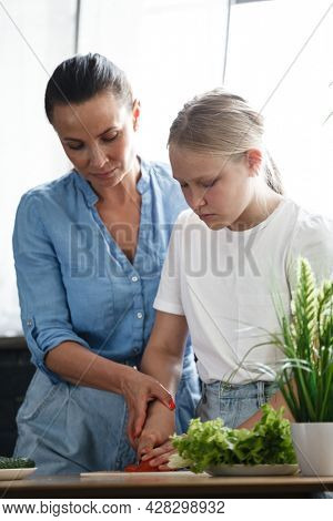 Healthy food at home. Happy family, mother and daughter are preparing salad. Woman and teenage girl are cutting vegetables in the kitchen