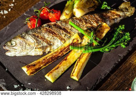 Rainbow trout grilled. Vegetables, white wine sauce. Delicious healthy traditional food closeup served for lunch in modern gourmet cuisine restaurant.