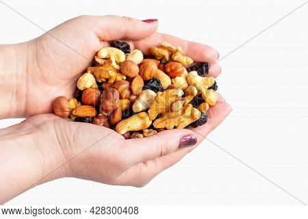 Close Up And Soft Focus Of A Woman's Hand With Nuts And Raisins Isolated On White Background. The Co