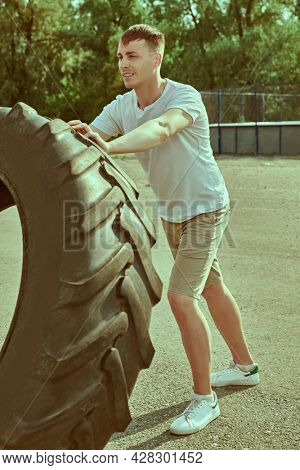 Active healthy lifestyle. Handsome muscular man is training with big tire at outdoor. Strength training.