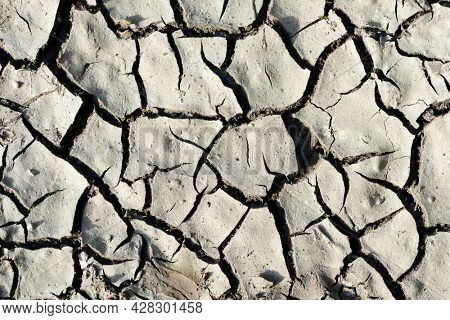 Arid cracked soil as background. Concept of climate change or global warming.