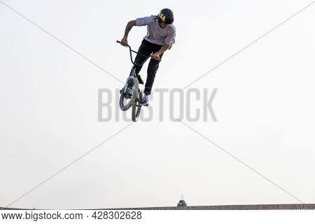 A Young Rider On A Bmx Bike Does Tricks In The Air