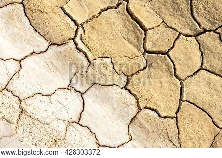 Dry Dewatered Sandy Ground. Global Warming Concept. Cracked Desert Soil. Arid Climate. Abstract Text