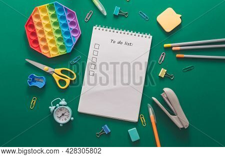 Colored Various School Supplies And An Alarm Clock On A Green Paper Background. Back To School And E