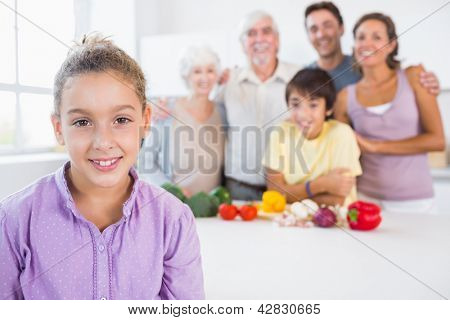 Young girl standing beside kitchen counter with family behind her