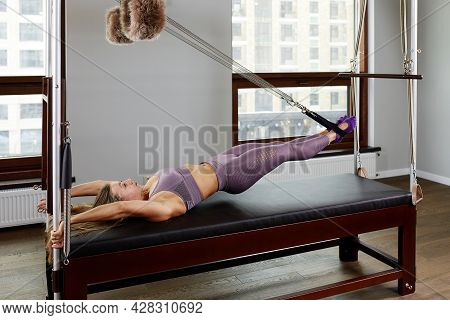 The Instructor Does Exercises On The Reformer, A Beautiful Girl Trains On The Modern Reformer Simula