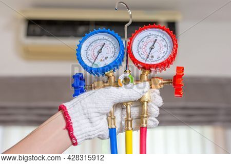 Air Conditioning Repair, Repairman Holding Monitor Tool To Check And Fixed Air Conditioner System