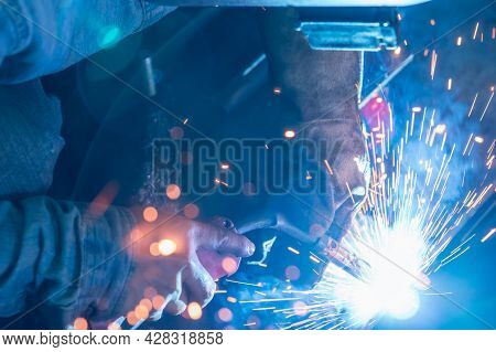 Welder Welding Metal With Argon Arc Welding Machine And Has Welding Sparks. A Man Wears Welding Mask