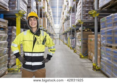 Smiling, hooded man, with a hard hat in a huge cold store warehouse