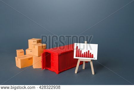 Boxes And Container Near The Easel With Falling Graph. Drop Of Transportation Volume, World Trade Tr