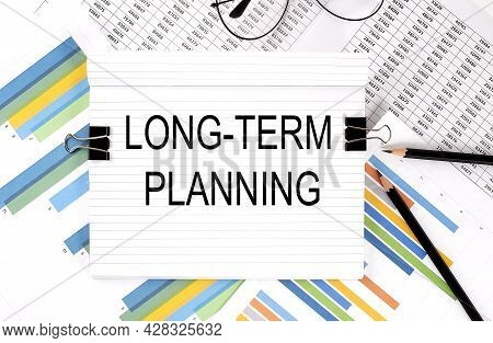 Notebook With Pencils, Glasses On Graph Background, With Text Long-term Planning