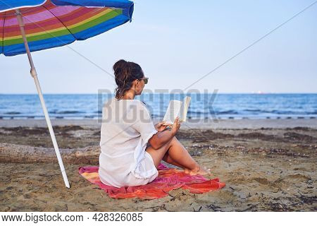 Traveler girl relaxing on tropical beach in vacation.Young girl traveler relaxing in vacation. Traveler relaxing on tropical beach in vacation. Girl in vacation relaxes on beach in summer day. Traveler. Summer. Vacations.