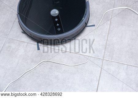 Robot Vacuum Cleaner On A Brown Floor. Obstacle In The Form Of Wires. The Robot Vacuum Cleaner Is En