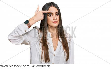 Young beautiful woman wearing casual white shirt pointing unhappy to pimple on forehead, ugly infection of blackhead. acne and skin problem