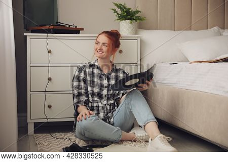 Young Woman Choosing Vinyl Disc To Play Music With Turntable In Bedroom