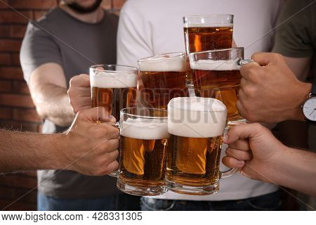 Friends Clinking Glasses Of Beer Near Red Brick Wall, Closeup