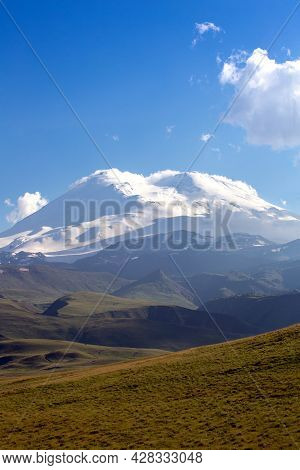 Snow-capped Mountain Peaks On A Summer Day. Elbrus On The Background Of Green Hills. Mountain Landsc