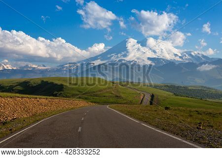 An Asphalt Road Leading To Snow-capped Mountain Peaks. A Summer Day. Elbrus On The Background Of Gre